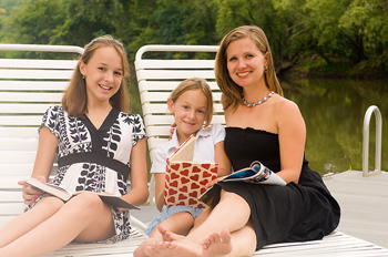Mother and daughters lounging by lake