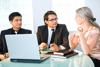 Businesspeople in conference room with laptop computer
