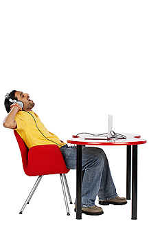 Man sitting at table listening to headphones
