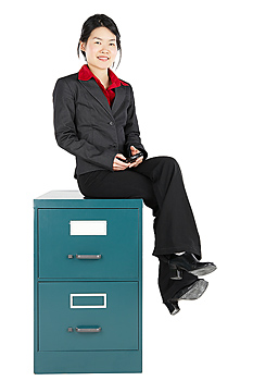 Businesswoman sitting on filing cabinet