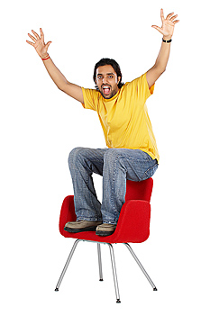 Man sitting on chair with arms raised
