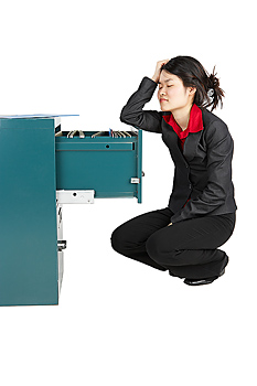 Businesswoman looking in filing cabinet
