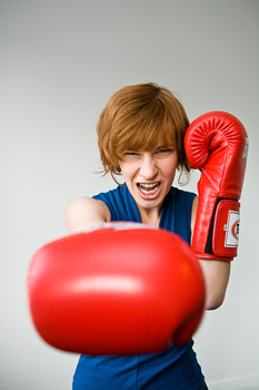 Portrait of woman wearing boxing gloves and punching