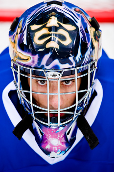 Portrait of intense hockey goalie in helmet and mask