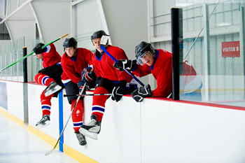 Angry hockey time climbing over wall of rink