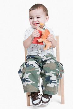 Studio shot of toddler boy in chair with toys