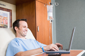 Hospital patient with laptop and smartphone