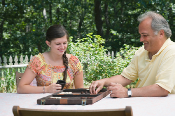 Father and daughter playing backgammon on table in backyard