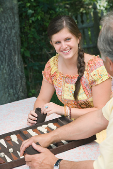 Teenage girl playing backgammon with father