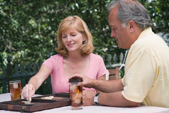 Couple playing backgammon on table in backyard