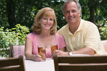 Couple posing at picnic table in backyard