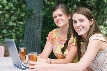 Teenage sisters with laptop on table in backyard