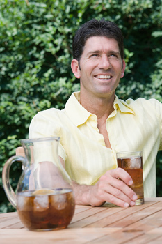 Man at table with ice tea outdoors