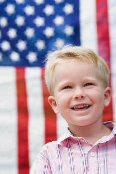 Blonde boy outdoors with American flag
