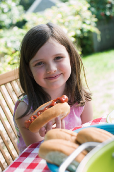 Girl posing at picnic table with hot dog