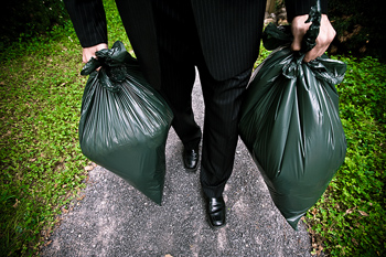 Waist down shot of man in suit carrying trash