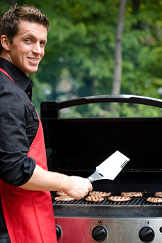 Man cooking hamburgers on grill