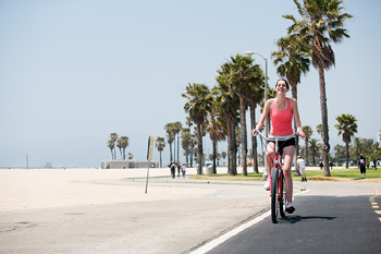 Woman riding bike along beach, Venice, California
