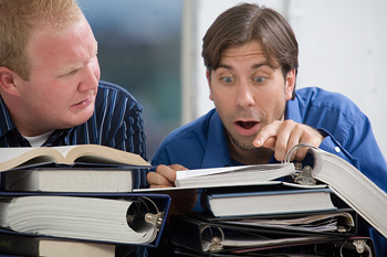 Businessmen searching through notebooks