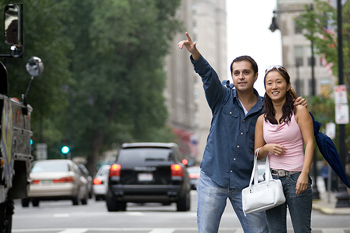 Tourist couple hailing taxicab on street