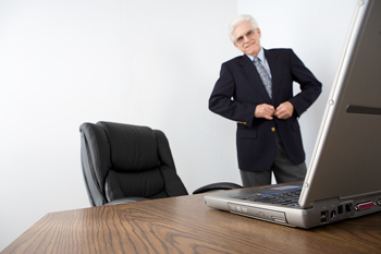 Man standing in office with laptop computer