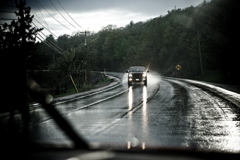 View from car of oncoming vehicle on rainy day