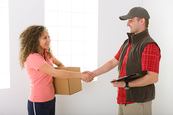 Woman shaking hands with courier after receiving box