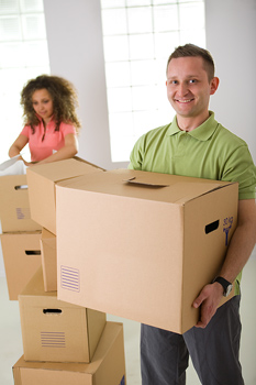 Smiling man with others carrying box