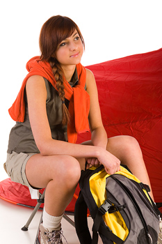 Daydreaming woman sitting by tent