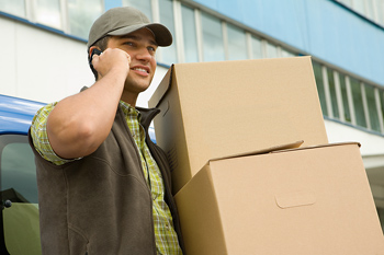 Courier with cell phone delivering boxes