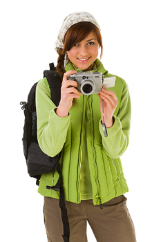 Smiling woman in outerwear with digital camera