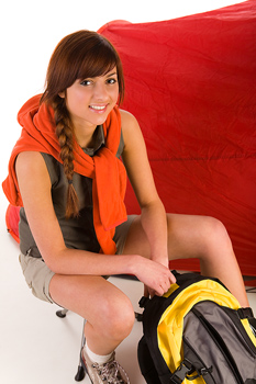 Smiling woman hiker posing with backpack and tent