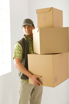 Smiling courier holding three boxes