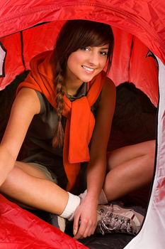Smiling woman sitting inside tent