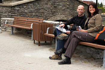 Smiling couple posing on bench in park