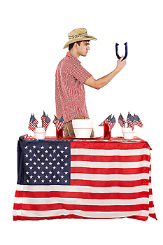 Man holding horseshoe by table with American flags
