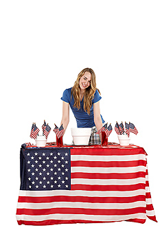 Woman posing by table decorated with American flags