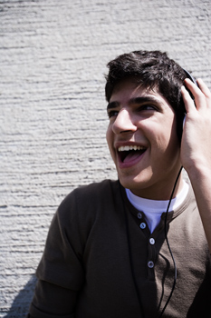 Young man listening to headphones outdoors