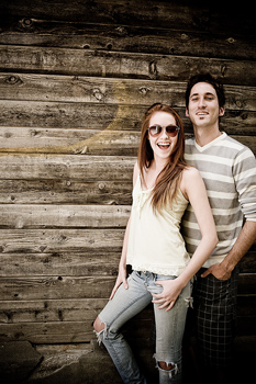 Couple posing together by wall
