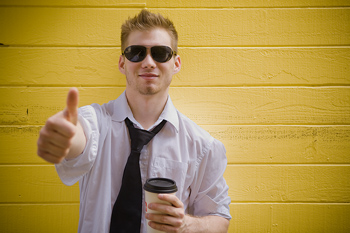 Hip man in sunglasses and tie gesturing thumbs-up