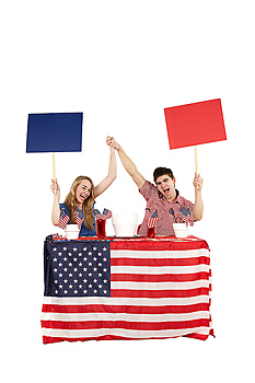 Excited patriotic couple sitting at table