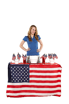 Woman posing by table with American flags