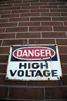 Wide angle view of sign warning of danger of high voltage