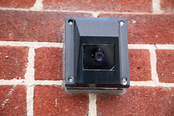 Security camera mounted on brick wall