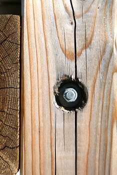 Bolt and nut in recessed cavity in wood