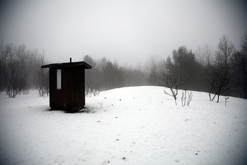 Fisheye view of outhouse in snow field