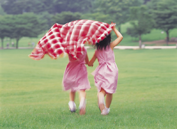 Girls running with blanket in park