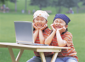 Girls making faces while using laptop