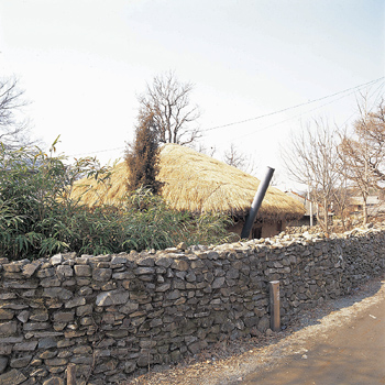 Village home in front of stone wall