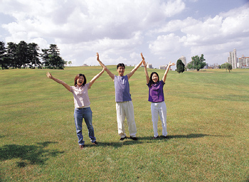 Friends in park with arms raised